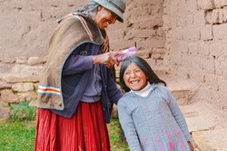 Happy native american grandmother combing hair of her granddaughter in the countryside.