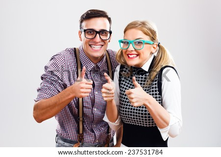 Happy nerdy couple showing thumbs up,Successful nerds