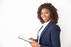 Happy new employee studying job instructions, holding documents, looking at camera. Young African American business woman standing isolated over white background. Career beginning concept