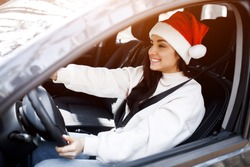 Happy New Year and Merry Christmas A woman is sitting in a car, she is wearing a red santaclaus hat and smiling