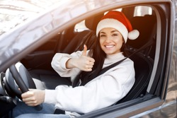 Happy New Year and Merry Christmas A woman sits in a car, she is dressed in a red Santaclaus hat and shows a thumb up