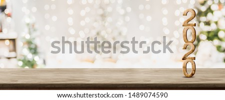 happy new year 2020 at woooden table top with abstract warm living room decor with christmas tree string light blur background with snow,Holiday backdrop,Mock up banner for display of product