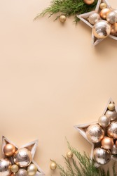 Happy new year background, merry christmas concept, gold decorations baubles in wooden stars with fir tree branches on light beige table pastel background, flat lay copy space top vertical view above