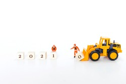 Happy new year 2021 background, miniature worker moving wooden cube with yellow front end loader turck