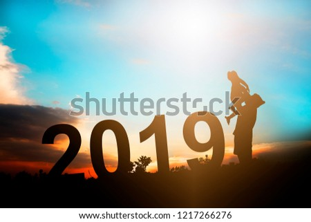 Happy new year 2019 background, silhouette mother carrying daughter to celebration together on filed in sunset  #1217266276