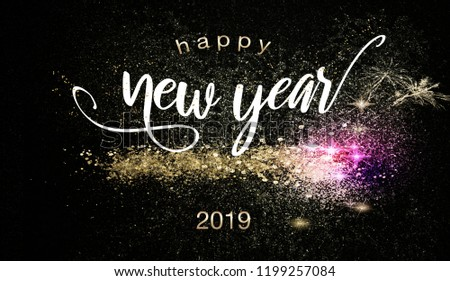 Happy New Year 2019 background with glittering gold and purple sparklers over a dark night background in a decorative design for a greeting card or invitation #1199257084