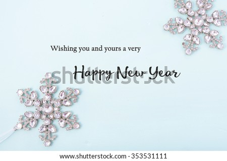 Happy New Year Background with snowflake ornaments on pale blue wood with sample text greeting.  #353531111
