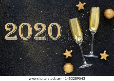Happy New Year 2020. Beautiful Glowing overlay for holiday greeting card. Flat lay composition. Beautiful Christmas golden trappings on black background. Copy Space. #1453289543