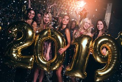 Happy new year! Beautiful young women in evening gown holding balloons and looking at camera with smile while celebrating in nightclub