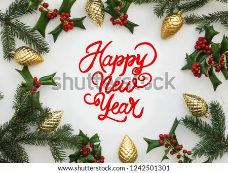 Happy New Year calligraphy lettering. Happy Holiday Greeting card inscription. Christmas wallpaper, flat lay, top view. Frame made of fir branches, red berries, fir and golden Christmas cones #1242501301