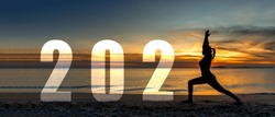 Happy new year card 2021. Silhouette lifestyle woman yoga practicing yoga standing as part of Number 2021 near the beach at sunset. Healthy and Holiday Concept