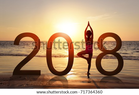 Shutterstock Happy new year card 2018. Silhouette of A girl doing Yoga vrikshasana tree pose on tropical beach with sunset sky background, watching the sunset, standing as a part of the Number 2018 sign.
