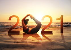 Happy new year card 2021. Silhouette of healthy girl doing Yoga Bow pose on tropical beach with sunset sky background, woman practicing yoga as a part of the Number 2021 sign.