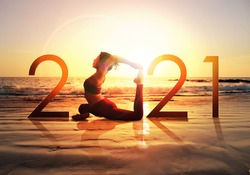 Happy new year card 2021. Silhouette of healthy girl doing Yoga One Legged Pigeon pose on tropical beach with sunset sky background, woman practicing yoga as a part of the Number 2021 sign.