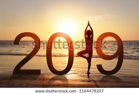 Happy new year card 2019. Silhouette of healthy girl doing Yoga vrikshasana tree pose on tropical beach with sunset sky background, watching the sunset, standing as a part of the Number 2019 sign. #1164478207
