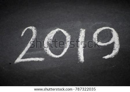 Happy new year card. 2019 text handwritten on scratched blackboard or chalkboard #787322035