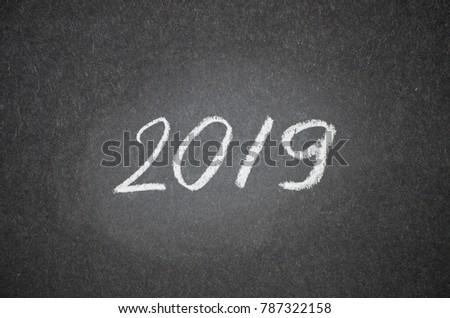Happy new year card. 2019 text handwritten on scratched blackboard or chalkboard #787322158