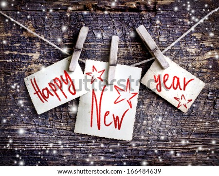 Happy New Year card with  snow on wooden background