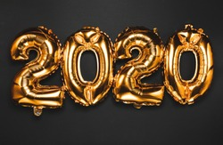 Happy New year 2020 celebration. Bright gold balloons figures, New Year Balloons with glitter stars on dark background. Christmas and new year celebration. Gold foil balloons 2020