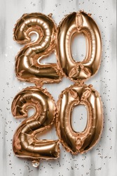 Happy New year 2020 celebration. Bright gold balloons figures, New Year Balloons with glitter stars on wood white background. Christmas and new year celebration. Gold foil balloons 2020