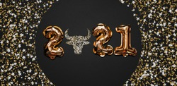 Happy New year 2021 celebration. Bright gold balloons figures, New Year Balloons with glitter stars on dark background. Christmas celebration. Gold foil balloons With symbol of the year of the bull