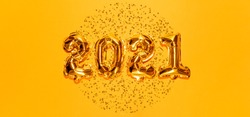 Happy New year 2021 celebration. Bright gold balloons figures, New Year Balloons with glitter stars on bright yellow background. Christmas and new year celebration. Gold foil balloons 2021 gift card