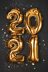 Happy New year 2021 celebration. Bright gold balloons figures New Year Balloons with glitter stars on dark background. Christmas and new year celebration. Gold foil balloons numeral 2021 and confetti
