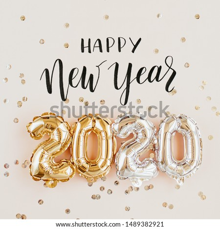 Happy New year 2020 celebration. Gold and silver foil balloons numeral 2020 and confetti on pink background. Flat lay