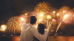 Happy new year 2020 celebration. Young couple new year fireworks countdown. Romantic couple under fireworks on sky.