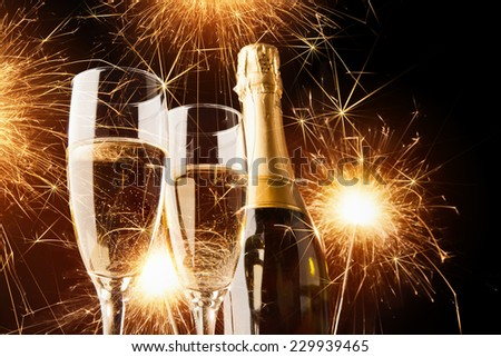 Happy new year, champagne with sparklers on dark background