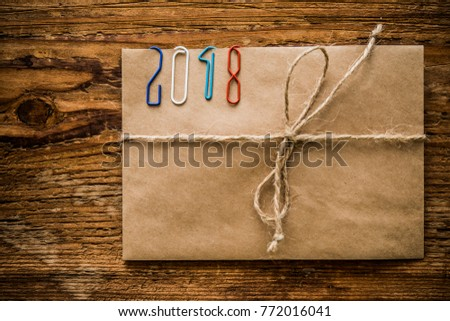 Happy new year 2018 - clips on paper envelope with rope lie on wooden table. Christmas background. holiday background. envelope wishes for Santa Clause. wish list for Santa Claus inside