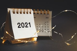 Happy new year 2021. Close up calendar and garland glowing on desktop