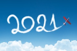 Happy New year 2021 concept on the background below cloudscape. Drawing by passenger airplane white vapor contrail in sky