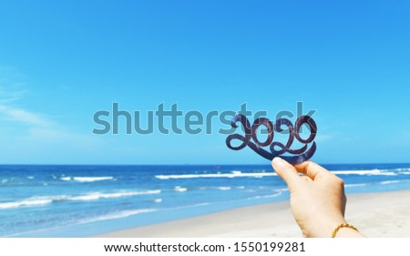 Happy New Year creative concept, hand holding 2020 text against blue sky and beach blur defocused background.