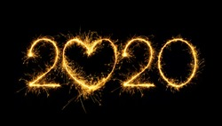 Happy New Year 2020. Creative Number 2020 with sign heart written sparkling sparklers isolated on black background for design. Beautiful Glowing overlay template for holiday greeting card.