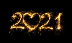 Happy New Year 2021. Creative Number 2021 with sign heart written sparkling sparklers isolated on black background for design. Beautiful Glowing overlay template for holiday greeting card.