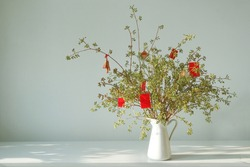 Happy New year decoration with vase flower on a white table. Lucky charm and red envelop decoration of apricot flower branch at home for wishing lucky on lunar Chinese new year