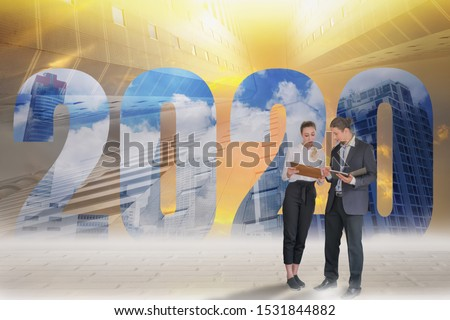 Happy New Year 2020 Digital Trend Concept,businessman and businesswoman stand to discuss company plans,goals and future planning new marketing trending,with background of skyscrapers and evening sky