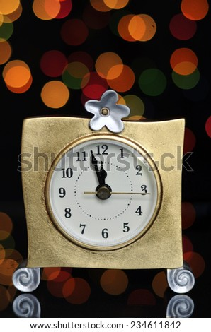 Happy New Year Eve party with gold clock and minutes to midnight time on reflective table against bright color festive bokeh lights.