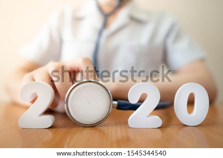 Happy New Year for health care and medical concept. Doctor in white uniform holding stethoscope with number 2020 on doctor desk. Idea for new trend in medicine treatment and diagnosis.