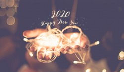 happy new year 2020 glowing word over hand with party light  string bokeh in vintage filter,Holiday, new year season.