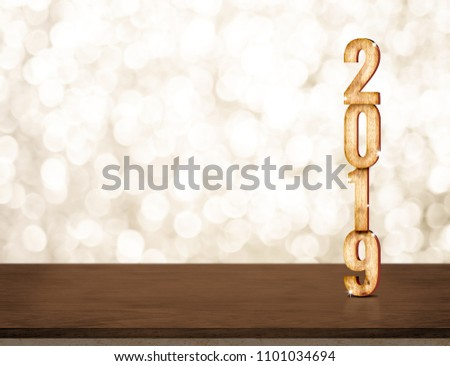 Happy New Year 2019 gold glossy with sparkling star on dark brown table with gold bokeh wall,Holiday festive celebration concept.copy space for display of text or content #1101034694