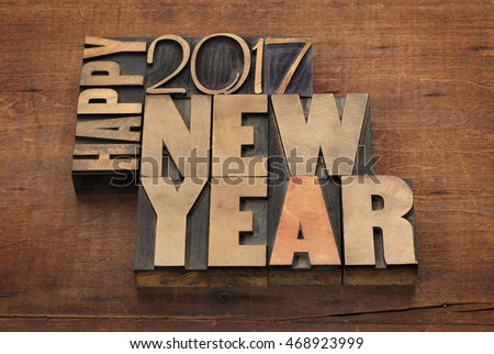 Happy New Year 2017 greeting card - text in vintage letterpress wood type blocks on a grunge wooden background #468923999