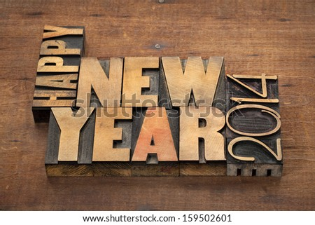 Happy New Year 2014 greetings or wishes - text in vintage letterpress wood type blocks on a grunge wooden background