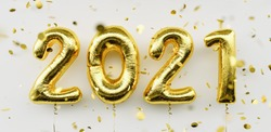 Happy New 2021 Year. Holiday gold metallic balloon numbers 2021 and falling confetti on white background