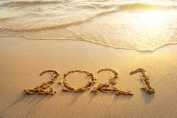 Happy New Year 2021, lettering on sunrise beach with wave in the morning. Numbers 2021 year on the sea shore, message handwritten in the golden sand on beautiful beach background. New Years concept.