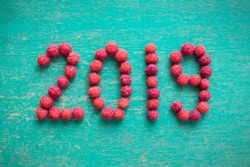 happy new year 2019 made of berries on a blue wooden background