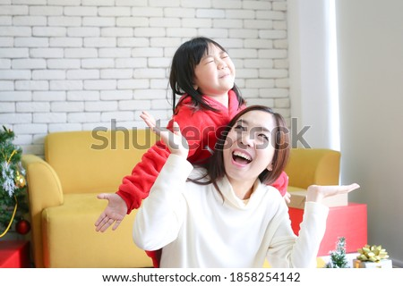 Photo of  Happy New year. Mom gives gifts to children. Cute girl gives his beloved mother a gift. Mother and daughter are happy on Christmas day.