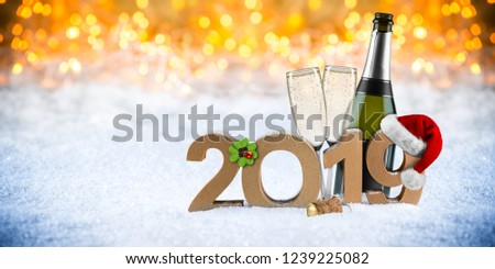 happy new year 2019 number with santa hat four leaf clover champagne bottle glass in front of golden bokeh lghts panorama snow background #1239225082