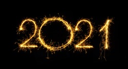 Happy New Year 2021. Number 2021 written with sparkling sparklers isolated on black background With Copy Space For Text. Beautiful Glowing overlay template for holiday greeting card.
